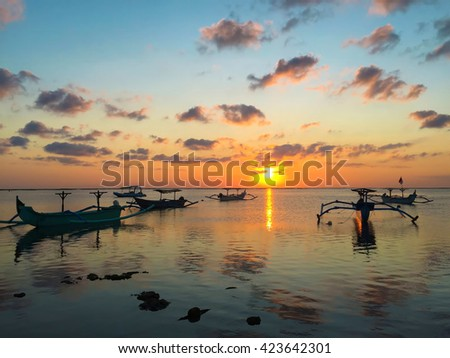 Traditional fishering boat in sunset sea, traditional boats of Bali, Bali sea during sunset, Sea and sunset sky, sunset sky reflections in quiet sea, fishering on sunset, sunset sea view with boats - stock photo