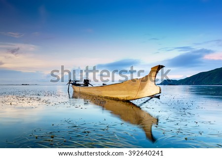 Traditional fishing boat during blue hour at Kuta, Lombok, Indonesia. (Image may contain noise and long exposure motion blur) - stock photo
