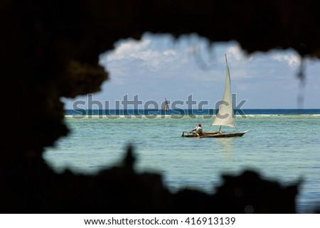 Traditional fishing boat floating on ocean in Zanzibar, Tanzania. - stock photo