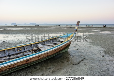 Traditional fishing boat on sandy beach in low tide, Thailand