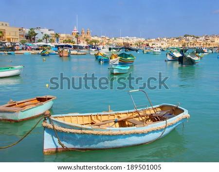 traditional fishing boats in the harbor of Marsaxlokk , Malta  - stock photo