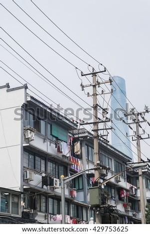Traditional flat residential building with Shanghai tower - clothes in a traditional alley - The Shanghai Tower is a megatall skyscraper in Lujiazui, Pudong, Shanghai. - stock photo