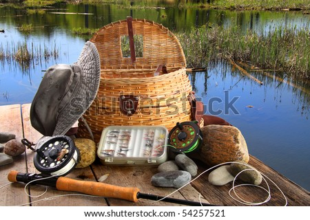 Traditional fly-fishing rod with equipment beside a lake - stock photo