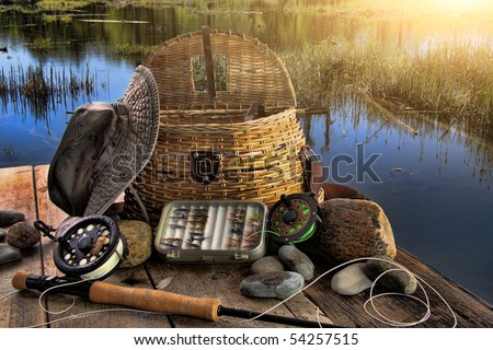 Traditional fly-fishing rod with equipment beside a lake late afternoon - stock photo