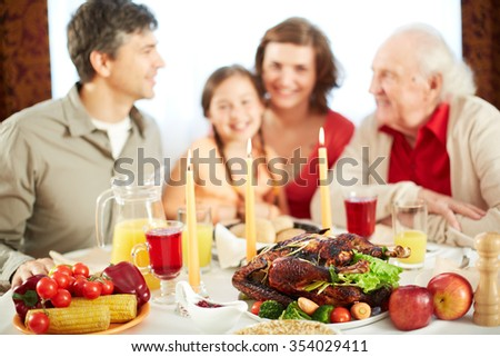 Traditional food and burning candles on background of family - stock photo