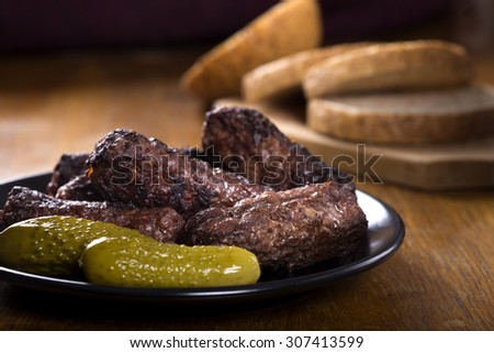 "Traditional food ""mici"" spicy meat balls on plate with pickled cucumbers - stock photo"