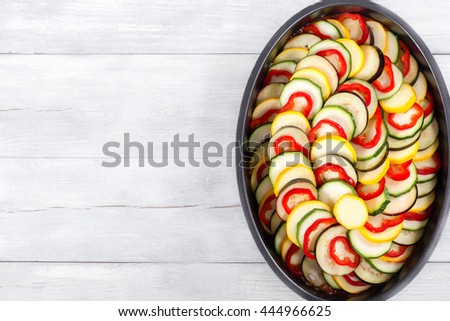 traditional French casserole ratatouille -  sliced summer vegetables with tomato sauce and spices prepared for baking in oven, view from above - stock photo