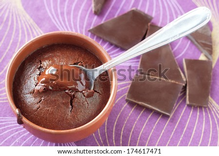 Traditional french chocolate fondant cake with melted heart in natural brown earthenware cup with a spoon. Natural blown and purple background with broken chocolate pieces. - stock photo