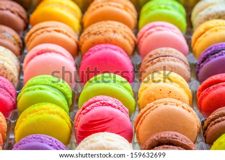 Traditional french colorful macarons in a rows in the box. There are sweet meringue-based confection which are often confused with the macaroons. - stock photo