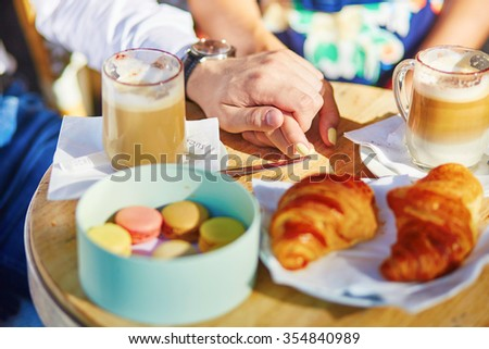 traditional French croissants and macaroons in a cozy outdoor cafe in Paris, France - stock photo