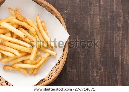 Traditional french fries in basket on wooden background. - stock photo