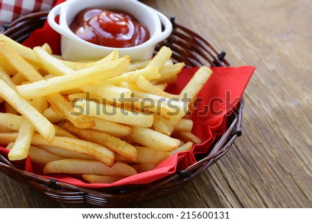 Traditional French fries with ketchup in a wicker basket - stock photo