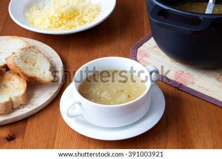 Traditional French onion soup with croutons and melted cheese on top in a ramekin. French cuisine - stock photo