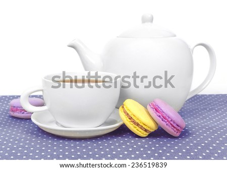 Traditional french pastry - macaroon with cup of tea on violet background