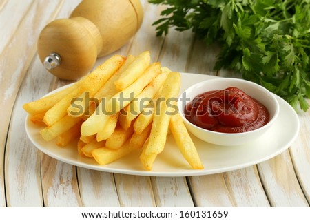 Traditional French potato fries with tomato ketchup - stock photo