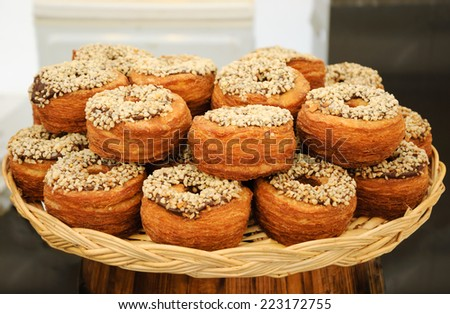 Traditional French puff  doughnuts pastries  with chocolate and nut topping for sale at food market in Paris. - stock photo