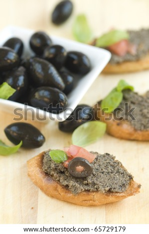 Traditional fresh tapenade - olive paste on bread - stock photo