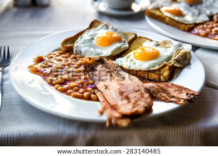 Traditional full english breakfast. Sunny-side-up fried eggs, baked beans, bacon and toast - stock photo