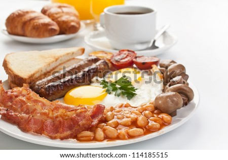 Traditional Full English Breakfast - sunny-side-up fried eggs, sausages, beans, mushrooms and bacon - stock photo