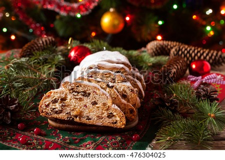 Traditional German Dresdner Christmas cake Stollen with Berries and Nuts Raising on a rustic wooden festive table. Holiday xmas celebration baking fruitcake. Atmospheric, cozy, romantic decorations.