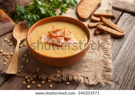 Traditional german homemade pea soup recipe with bacon and croutons in clay dish on vintage wooden table background. Tasty national food. Rustic style. - stock photo