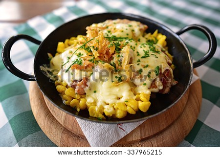 """Traditional german meal, called """"Bergpfandl"""", specific to the Berchtesgaden Alps area, Bavaria. It is a delicious dish with fillet of pork with spaetzle and fresh mushrooms, gratinated with cheese. - stock photo"""
