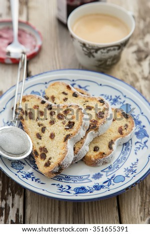 Traditional german Stollen with raisins and powdered sugar, on white and blue ceramic plate on wooden table. With espresso and jam. Traditional Christmas baking. Selective focus. Natural light