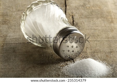 Traditional glass salt cellar and spilled salt on a wood background  - stock photo