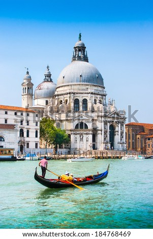 Traditional Gondola on Canal Grande with Basilica di Santa Maria della Salute in the background at sunset, Venice, Italy - stock photo