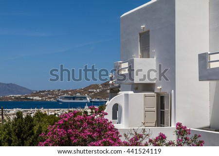 Traditional greece white house with oleander rose bay flowers on sea background with ships and ferry boats - stock photo