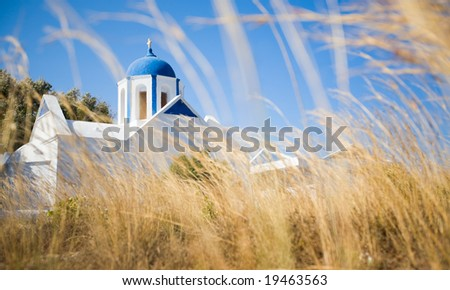 Traditional Greek blue domed church in field on beautiful island of Santorini, Greece - stock photo