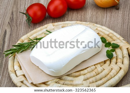 Traditional Greek cheese - Feta with herbs on the wood background