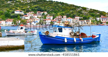 Traditional Greek fishing harbour with boats white houses by the sea. Panoramic view. - stock photo