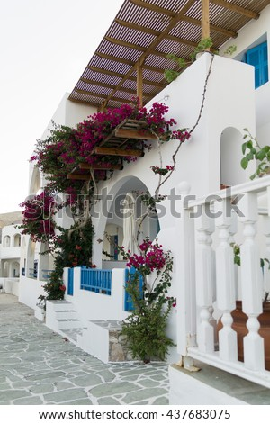 Traditional greek islands white house with blue decoration and oleander rose bay flower - stock photo