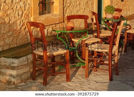 traditional greek outdoor restaurant on terrace, empty table at an street village restaurant, Crete, Greece. Sunset light - stock photo