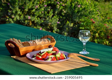 Traditional Greek salad served on table - stock photo