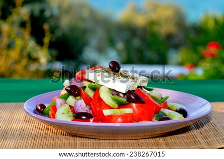 Traditional Greek salad served on table in front of Mediterranean sea - stock photo