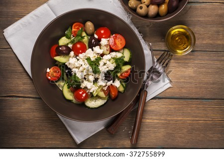 Traditional greek salad with fresh vegetables, feta cheese and olives. Top view. Rustic style. Selective focus - stock photo