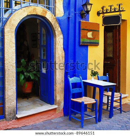traditional greek streets with small tavernas - stock photo