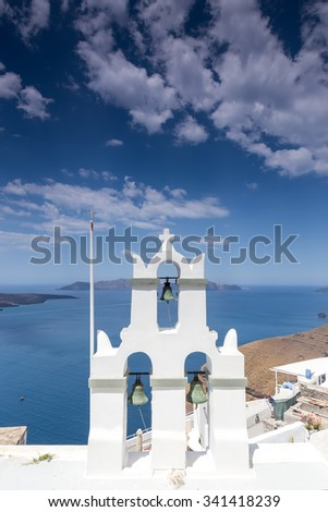 Traditional Greek white church arch with cross and bells in village Fira of Cyclades Island Santorini Greece - stock photo