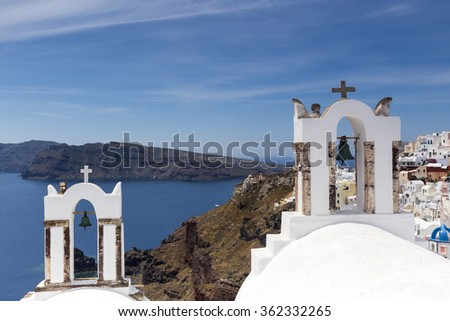 Traditional Greek white church arch with cross and bells in village Oia of Cyclades Island Santorini Greece