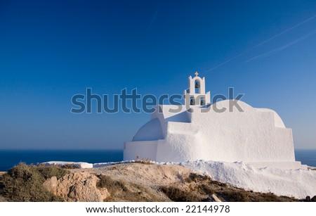 Traditional Greek white church near seashore on beautiful island of Santorini, Greece - stock photo
