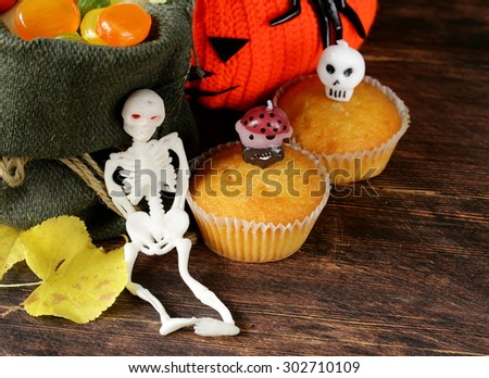 traditional halloween treats cupcakes with funny candles - stock photo