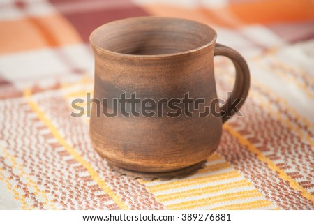 Traditional handcrafted mug on the multycolor background