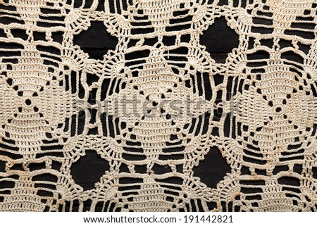 Traditional handmade embroidery made with thin twine in Greece on black wooden table