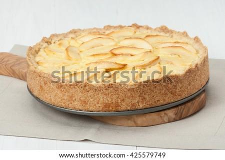 Traditional Homemade Apple Pie With Creamy Custard. Linen Napkin. Olive Wood Board - stock photo