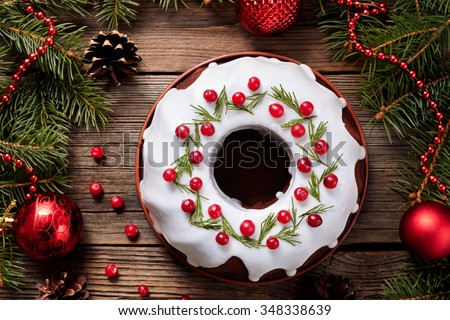 Traditional homemade christmas cake holiday dessert with cranberry in new year tree decorations frame on vintage wooden table background. Rustic style. Top view - stock photo