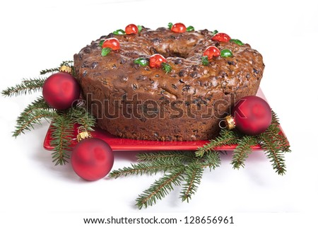 Traditional homemade Christmas fruitcake decorated with candied cherries, boughs and baubles