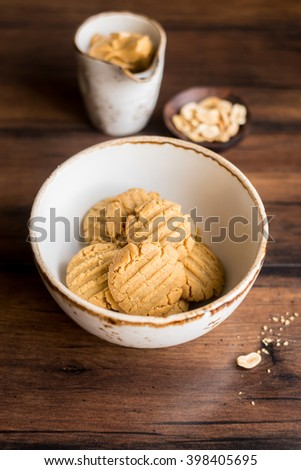 Traditional homemade peanut butter cookies with nuts and oat flakes in a bowl, selective focus - stock photo
