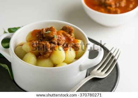 traditional homemade potato gnocchi with tomato puree and grated parmesan in white bowl - stock photo